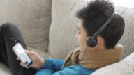 Teenager boy Enjoy Listening to Music on the sofa in relax time , Lifestyle and Relaxation concept