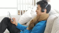 Teenager boy Enjoy Listening to Music on the sofa in relax time , Lifestyle and Relaxation concept , panning right to left movement