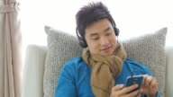 Teenager boy Enjoy Listening to Music on the sofa in relax time , Lifestyle and Relaxation concept , Panning left to right movement