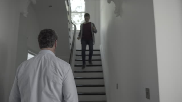 Teenager boy on staircase towards mature adult father