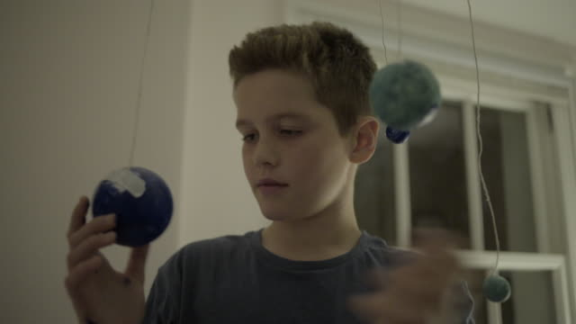Teenager boy playing with globes in bedroom