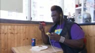 / teenager buys and eats pizza and a soda at a Bronx NY pizza parlor / Sits down and immediately uses cell phone and iPod while eating Pizza and...