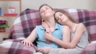 Teenager couple resting indoors, boy listening to music through headphones