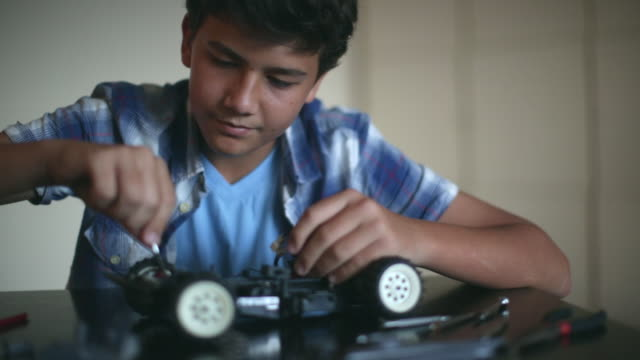 CU Teenager fixing a remote control car