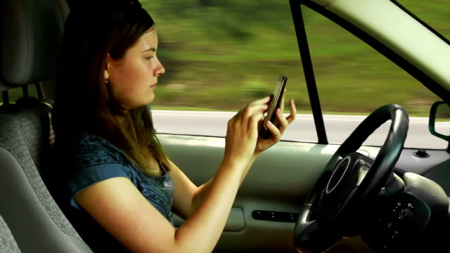 Teenager girl driving a car and playing with smart phone