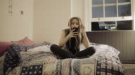 Teenager girl in bedroom on smart phone with headphones