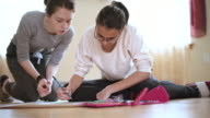 Teenager girl make homework shool project, and older sister help her.