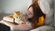 Teenager girl petting the red tabby cat lying in the bed at the morning