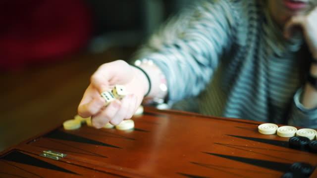 Teenager girl play backgammon, throwing dice