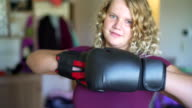 Teenager girl wearing boxing gloves practicing fighting
