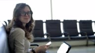 Teenager girl working with the smartphone and tablet in the airport lounge