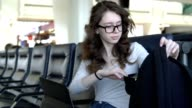 Teenager girl working with the smartphone and tablet in the airport lounge, then packing them into the backpack
