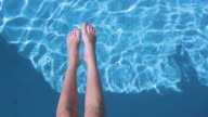Teenager girl's legs in the water of the backyard's pool