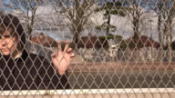 Teenager / Hoody staring through wire fence