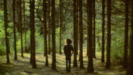 Teenager is contemplating in the forest / Teen walks into the forest / Forest Walk on October 01 1970 in Farmington Utah