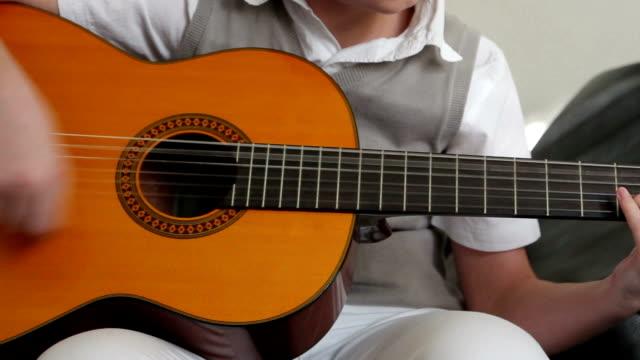 Teenager playing guitar (closeup)
