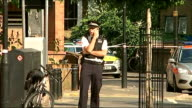 Teenager stabbed in Stoke Newington ENGLAND London Stoke Newington EXT Police cordon tape across road Police officer using mobile phone Trees in park...