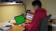 teenager typing at a laptop with green screen