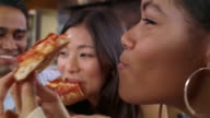 Teenagers eating pepperoni pizza at restaurant / girl covering mouth and laughing