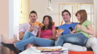 HD DOLLY: Teenagers Eating Pizza And Watching TV