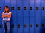Teenagers leaning on lockers in school hallway