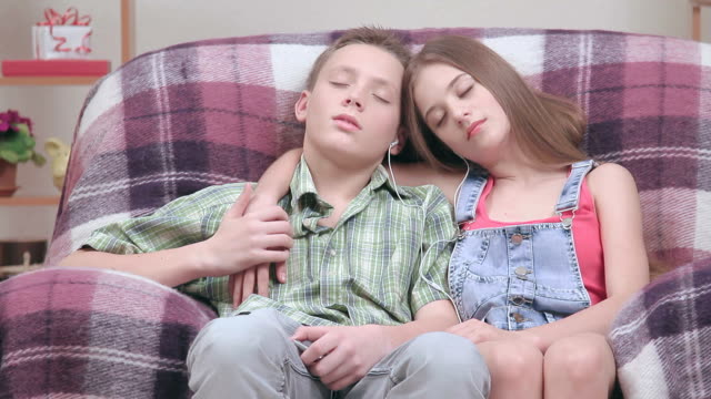 Teenagers relish in armchair, girl and boy falling asleep.