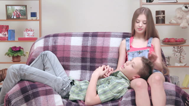 Teenagers resting indoors together: boy lie on her knees.