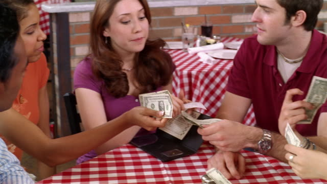 Teenagers splitting check at pizza restaurant