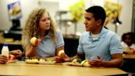 Teenager reden über Mittagessen in der cafeteria der Schule