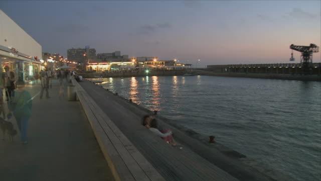 T/L WS Tel Aviv's sea port at dusk with tourists / Tel Aviv, Dan metropolitan, Israel