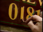 Telephone numbers about to change ITN LIB Sign writer's hand painting in '1' to number Avon Bristol INT LA MS Sign in office '16 April 1995 PHONEDAY'...
