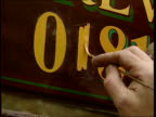 Telephone numbers about to change ITN LIB Sign writer's hand painting in '1' to number CBV Sign writer at work
