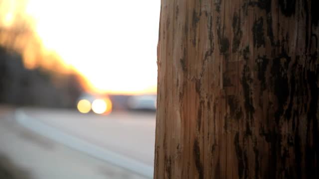 Telefonmast den Vordergrund, während Autos gehen durch