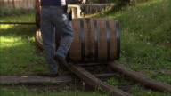 Telephoto close up of employee rolling a barrel of bourbon on to rail line.
