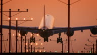 Telephoto - jumbo jet enters frame, lands at sunset in silhouette: Airbus A340