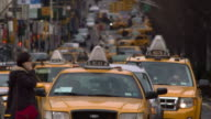 A telephoto shot of Park Avenue South on coming traffic, taxi's and street signs compressed.  People walk through crosswalks