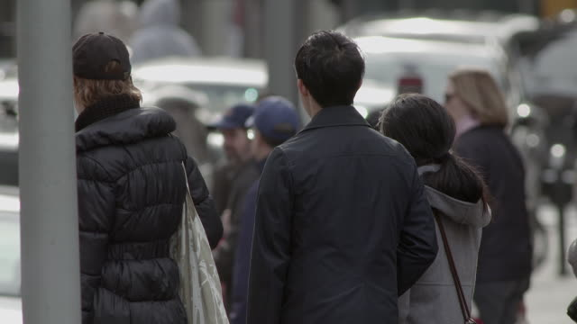A telephoto shot of people waiting to cross the street at a bus stop.
