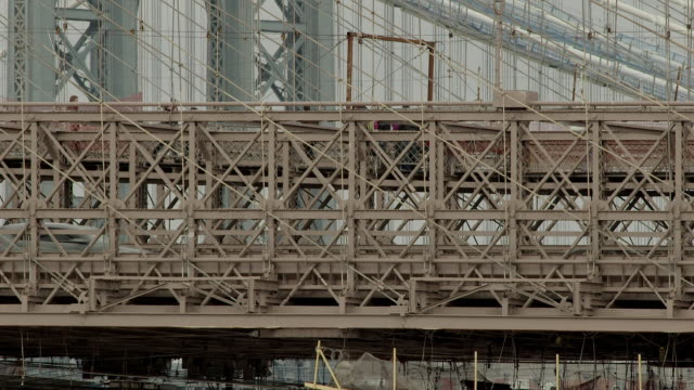 Telephoto shot of people walking over the Brooklyn Bridge.  Car traffic is below