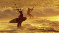 Telephoto shot of several kitesurfers in action during sunset
