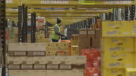 Telephoto view through rows of stacked boxes at a large food distribution warehouse in the UK.