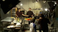 WS, Television crew filming chef preparing food in commercial kitchen