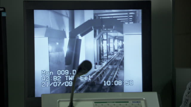 Television monitor shows view of metro tracks; monitor shows network of train tracks.