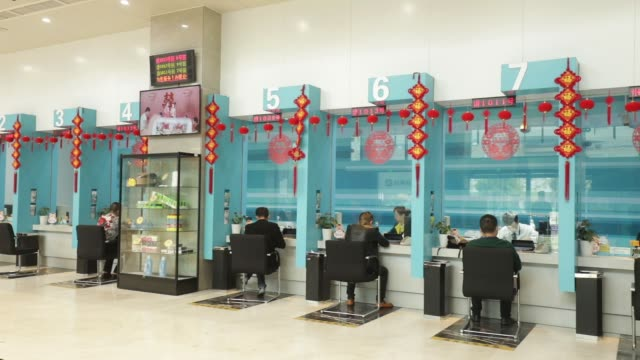 Tellers attend to customers at the Bank of Taizhou Co Ltd's headquarters in Taizhou China on Tuesday Nov 7 A teller attends to a customer A teller...