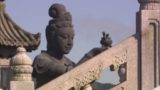 A temple statue holds an offering to Buddha.