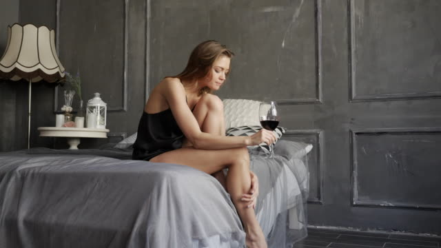 Tempting woman in black pajamas sitting on the bed with a glass of wine
