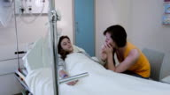 Tenage girl is visited by her older sister in hospital