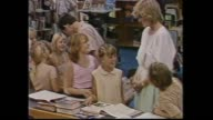 Kids waving Australian flags / Princess Diana meet and greet mostly indigenous people / Prince Charles with school girl flips through her book /...