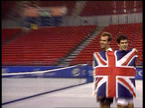 Birmingham Davis Cup ITN ENGLAND Birmingham Indoor Arena Tim Henman and Greg Rusedski pose on court wrapped in Union Jack as CBV photographer takes...