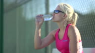 A tennis player drinking water between matches. - Slow Motion