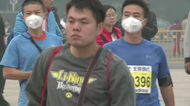 Tens of thousands of runners tackle hazardous air pollution in an annual marathon race held in Beijing